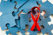 A red ribbon against a blue puzzle
