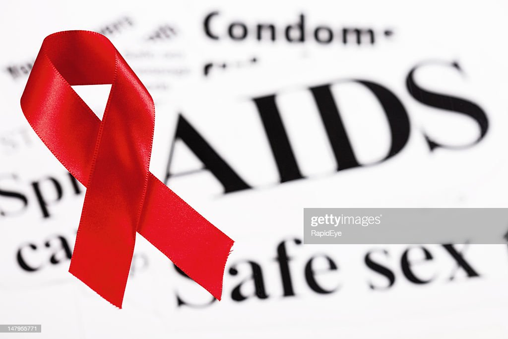 Red ribbon on AIDS and safe sex newspaper headlines : Stock Photo