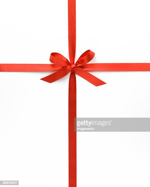 Red ribbon with bow against white background, close-up