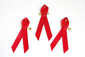 Red ribbons with golden pins for the Aids concept isolated on white