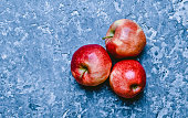 Red ripe apples on a concrete table. Fresh fruits. Loft and rustic style. Top view