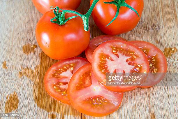 Red ripe tomatoes over a wooden cutting boarda more realistic approach to food ingredients the beauty of the imperfect