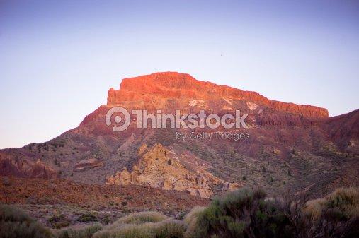 red rock facing the pico del teide vulcano at sunset stock photo