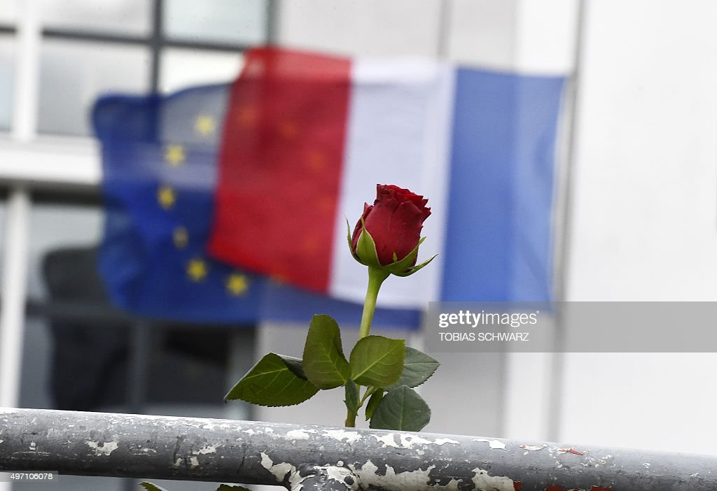 A red rose is placed in front of the French and the EU flag at halfmast outside the French Embassy in Berlin on November 14 a day after deadly...