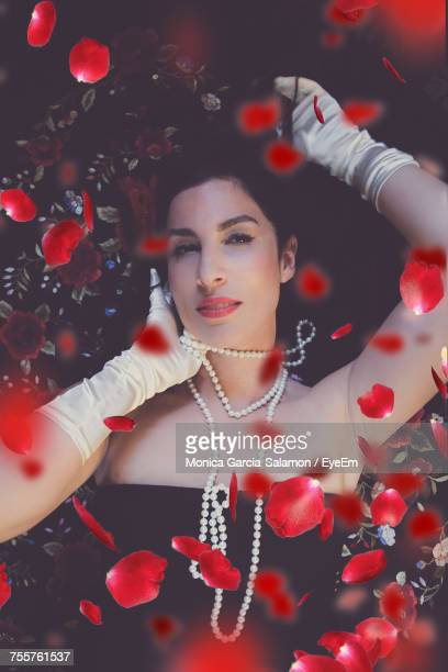 Red Rose Petals Falling On Female Fashion Model Lying On Bed