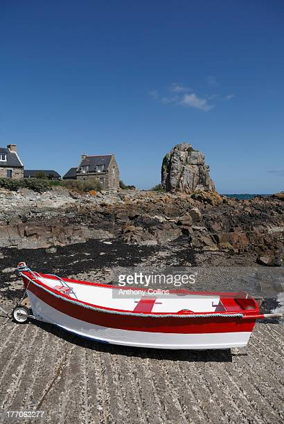 red rowing boat and rocky Breton coast