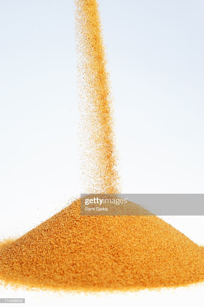 Red sand pouring out on mini dune : Stock Photo