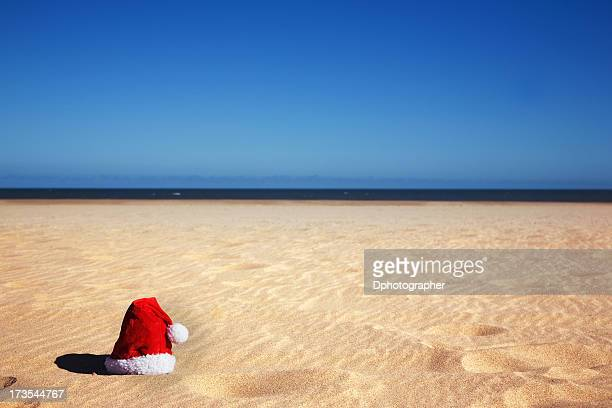 Red Santa hat on a sandy beach