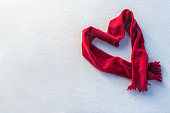 Red scarf as heart. Heart shape on snow. Valentine's day, love symbol, charity, winter season concept. Greeting card top view with copy space. Flat lay