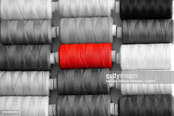 Red Sewing Thread Stands Out From Grey Ones