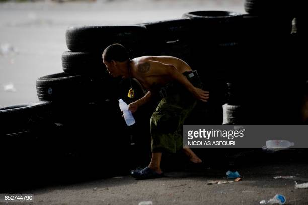 A ''Red Shirt'' anti government protester is seen behind tyres after several gun shots were heard hitting two men as hundreds of people gathered...