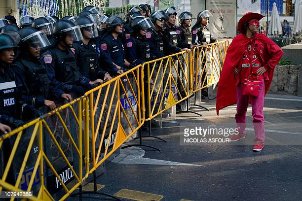 A 'Red Shirt' antigovernement protester stands in front of Thai riot police near Ratchaprasong intersection in Bangkok on January 9 2011 Red Shirts...