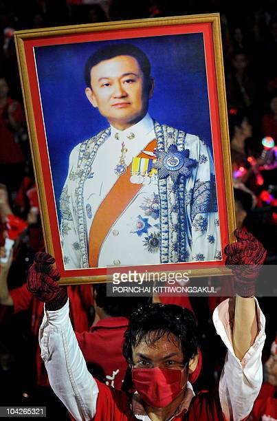 A 'Red Shirt' antigovernment protester holds a portrait of former Thai Prime Minister Thaksin Shinawatra during a protest in Chiang Mai province on...