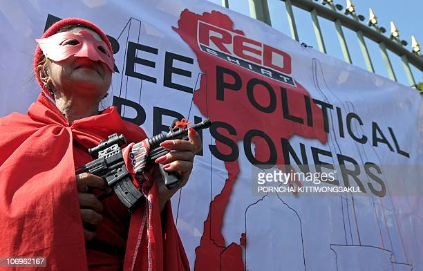 A 'Red Shirt' antigovernment protester holds a toy gun during a demonstration in front of a Bangkok prison on November 19 2010 Thai 'Red Shirts'...