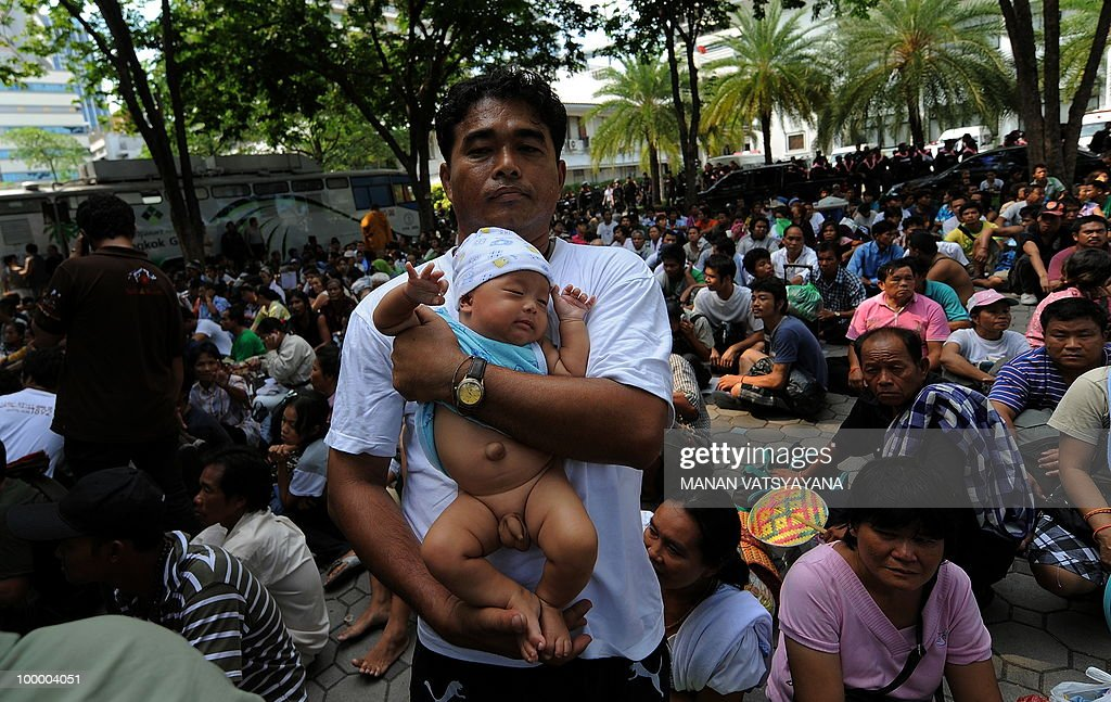 A Red Shirt anti-government protester holds his son at the Police headquarters in downtown Bangkok on May 20, 2010 after being moved from a temple which had been turned into a shelter within an anti-government protest site. Thai police escorted thousands of protesters out of a Buddhist temple where they had cowered overnight after nine people were killed there in gunbattles.