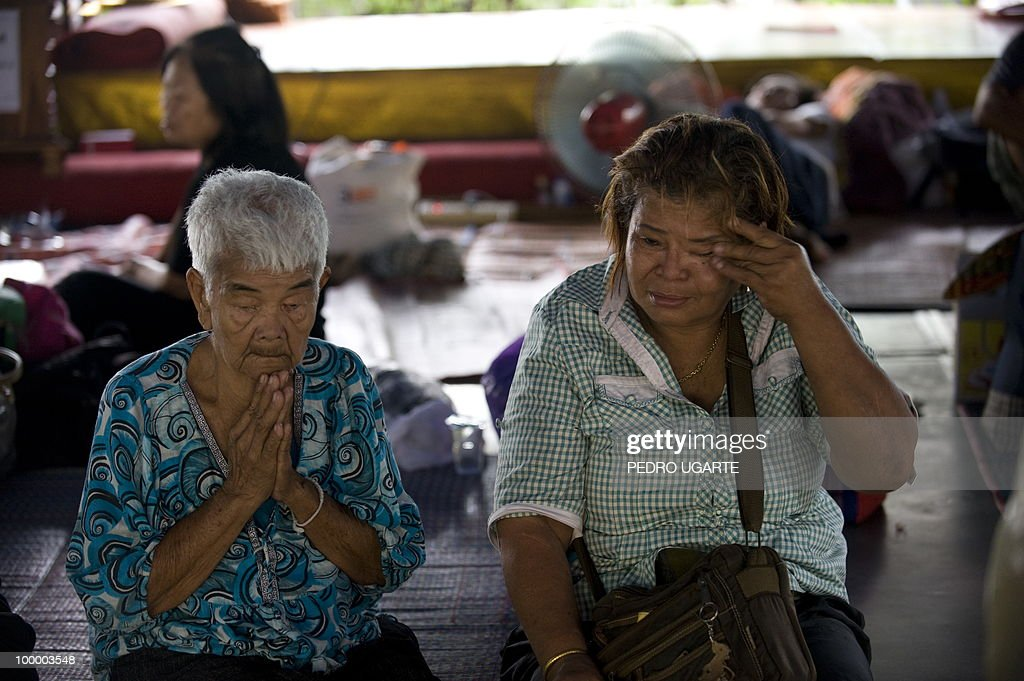 A Red Shirt anti-government protester wipes tears from his eyes moments before leaving a temple which had been turned into a shelter within an anti-government protest site in downtown Bangkok on May 20, 2010. Thai police escorted thousands of protesters out of a Buddhist temple where they had cowered overnight after nine people were killed there in gunbattles.