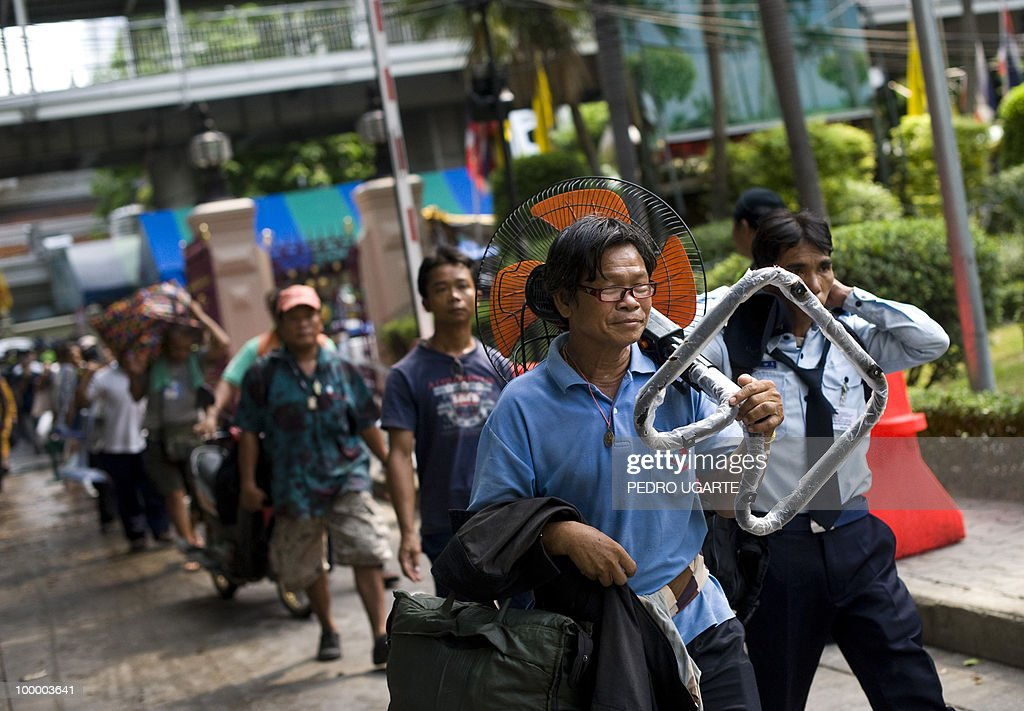 Red Shirt anti-government protesters carry their belongings they leave a temple which had been turned into a shelter within an anti-government protest site in downtown Bangkok on May 20, 2010. Thai police escorted thousands of protesters out of a Buddhist temple where they had cowered overnight after nine people were killed there in gunbattles.