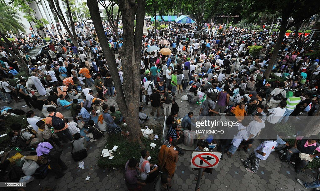 'Red Shirt' anti-government protesters gather at the police headquarters in downtown Bangkok on May 20, 2010 after being moved from a Buddhist temple. Thai police escorted thousands of protesters out of a Buddhist temple where they had cowered overnight after nine people were killed there in gunbattles. AFP PHOTO / Bay ISMOYO