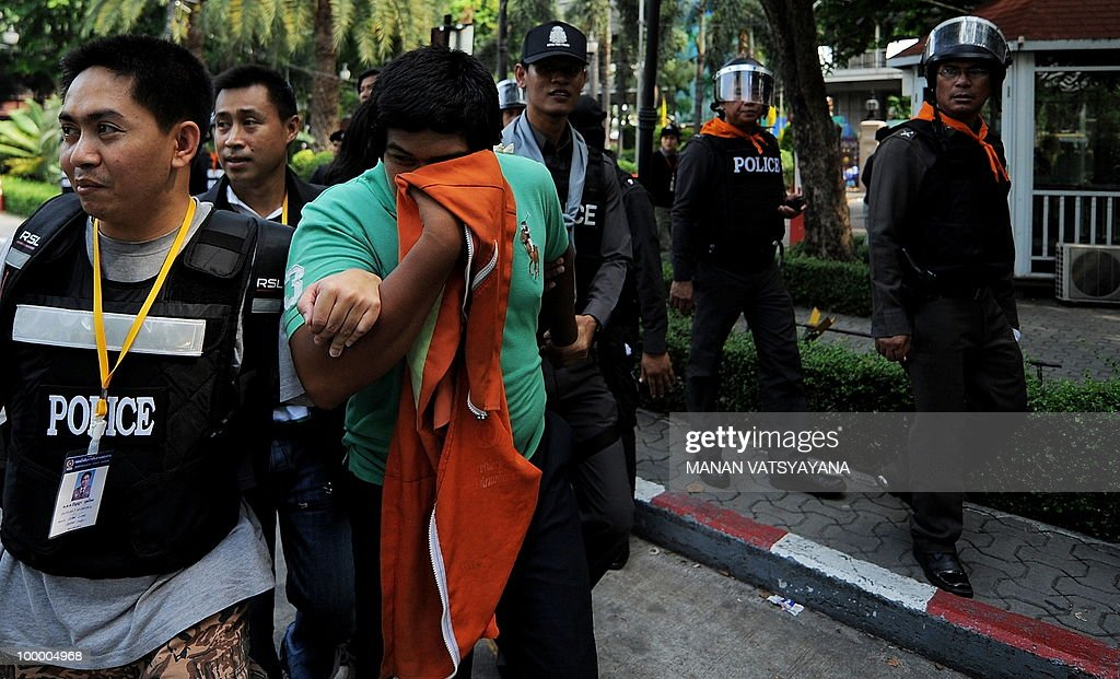 A 'Red Shirt' anti-government protestor covers his face as he is escorted to the police headquarters in downtown Bangkok on May 20, 2010 from a temple which had been turned into a shelter within an anti-government protest site. Thai police escorted thousands of protesters out of a Buddhist temple where they had cowered overnight after nine people were killed there in gunbattles.