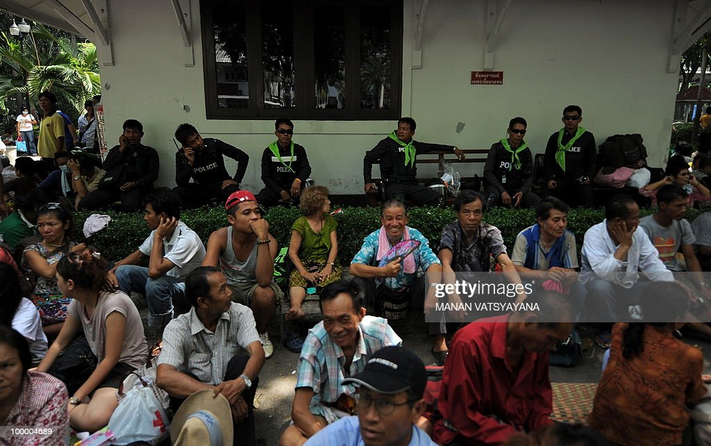 'Red Shirt' anti-government protestors sit on the floor at the police headquarters in downtown Bangkok on May 20, 2010 after bieng escorted from a temple which had been turned into a shelter within an anti-government protest site. Thai police escorted thousands of protesters out of a Buddhist temple where they had cowered overnight after nine people were killed there in gunbattles.