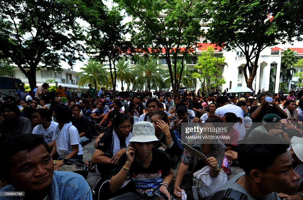 Red Shirt anti-government protestors sit on the floor at the police headquarters in downtown Bangkok on May 20, 2010 after bieng escorted from a temple which had been turned into a shelter within an anti-government protest site. Thai police escorted thousands of protesters out of a Buddhist temple where they had cowered overnight after nine people were killed there in gunbattles.