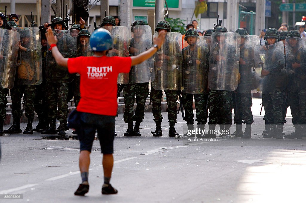 A red shirt protester gestures to members of the Thai military during violent protests on April 13, 2009 in Bangkok, Thailand. Anti-government protesters clashed with the military on the streets of Thailand's capital after the government declared a state of emergency. The pro-Shinawatra demonstrators are calling for the resignation of Prime Minister Abhisit Vejjajiva and for fresh elections to be held.