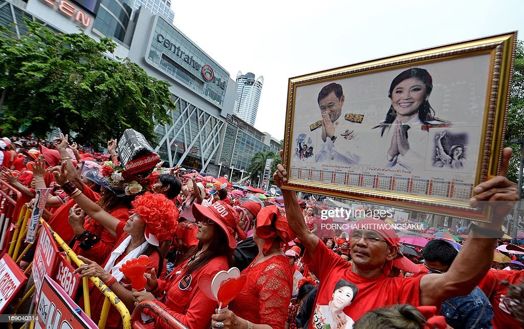 A 'Red Shirt' supporter (R) holds up a portrait of ousted Thai prime minister Thaksin Shinawatra and his sister, current Thai Prime Minister Yingluck Shinawatra (R), at a gathering to mark the third anniversary of the military crackdown on anti-government protesters in Bangkok on May 19, 2013. About 90 people were killed and nearly 1,900 wounded in a series of street clashes between demonstrators and security forces, which culminated in a military crackdown in May 2010. Two foreign journalists were among those killed.