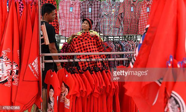 A 'Red Shirt' supporter of Thai Prime Minister Yingluck Shinawatra shops at a stall near the headquarters of the National AntiCorruption Commission...