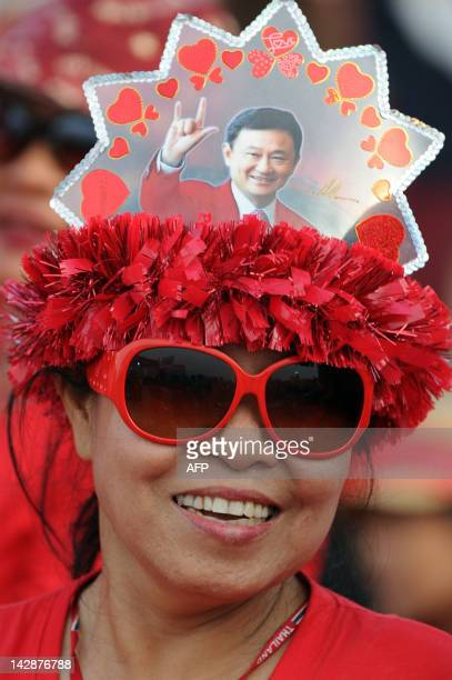 A 'Red Shirt' supporter of Thailand's fugitive former premier Thaksin Shinawatra smiles during a rally in Siem Reap province some 300 kilometers...