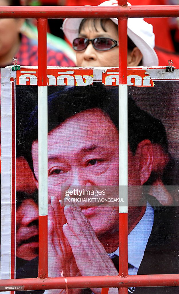 A 'Red Shirt' supporter sits behind a portrait of ousted Thai prime minister Thaksin Shinawatra at a gathering to mark the third anniversary of the military crackdown on anti-government protesters in Bangkok on May 19, 2013. About 90 people were killed and nearly 1,900 wounded in a series of street clashes between demonstrators and security forces, which culminated in a military crackdown in May 2010. Two foreign journalists were among those killed.