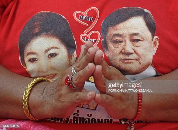 A 'Red Shirt' supporter wears a tshirt showing pictures of fugitive former premier Thaksin Shinawatra and Thai Prime Minister Yingluck Shinawatra...