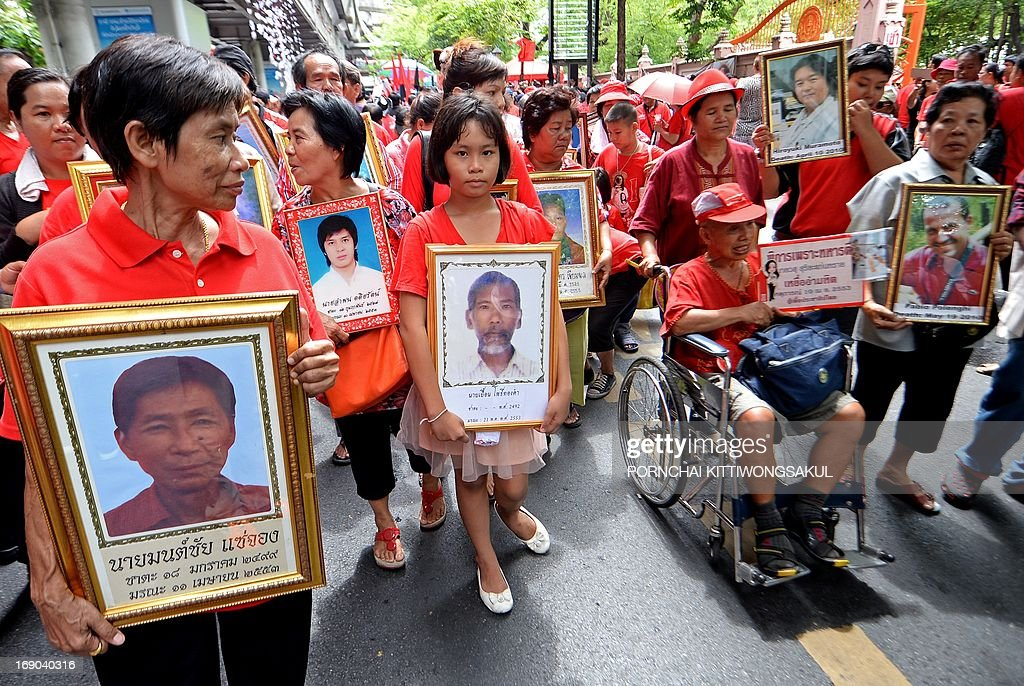 'Red Shirt' supporters hold portraits of protesters and journalists who died in 2010 unrest in the heart of the capital, as they gather to mark the third anniversary of the military crackdown on anti-government protesters at a Buddhist temple in Bangkok on May 19, 2013. About 90 people were killed and nearly 1,900 wounded in a series of street clashes between demonstrators and security forces, which culminated in a military crackdown in May 2010. Two foreign journalists were among those killed.