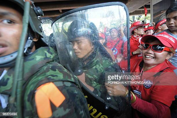 Red Shirt supporters of ousted Thai premier Thaksin Shinawatra manhandle soldiers as they break through a checkpoint during an antigovernment protest...