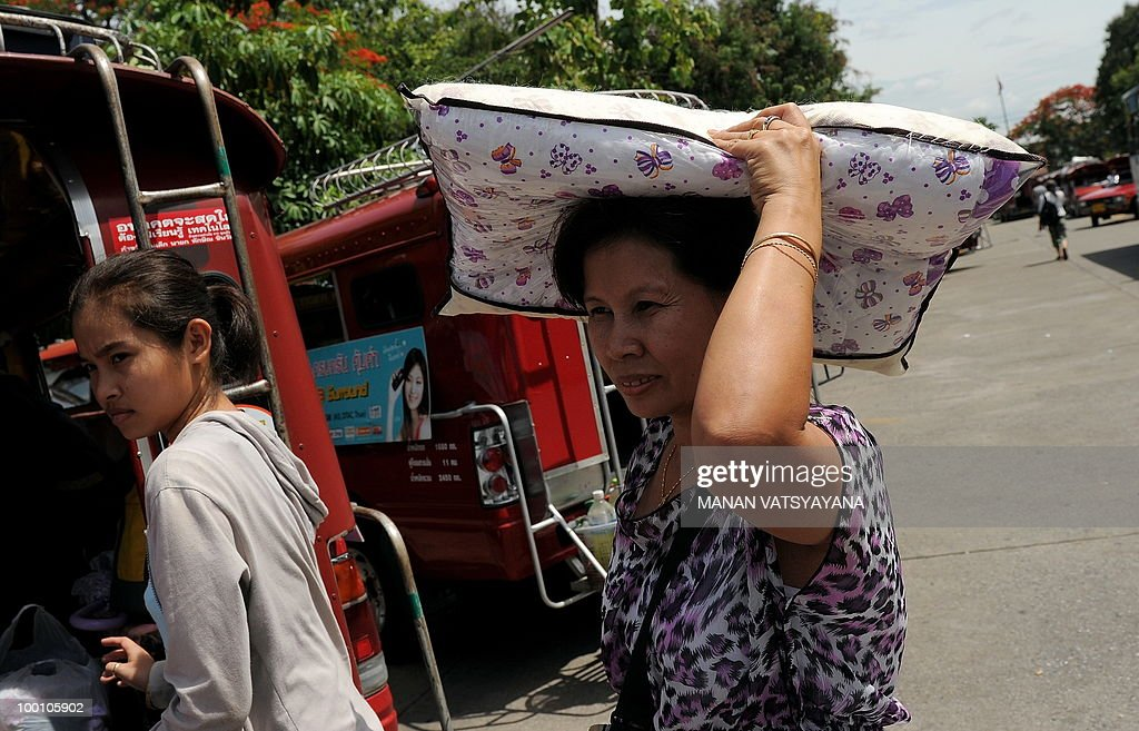 A Red Shirts protester carries her pillow after arriving on a train from Bangkok at the train station in Chiang Mai around 700kms from Bangkok on May 21, 2010. Thailand picked up the pieces after violence and mayhem triggered by a crackdown on anti-government protests, as the focus swung to recovery and reconciliation in a divided nation.