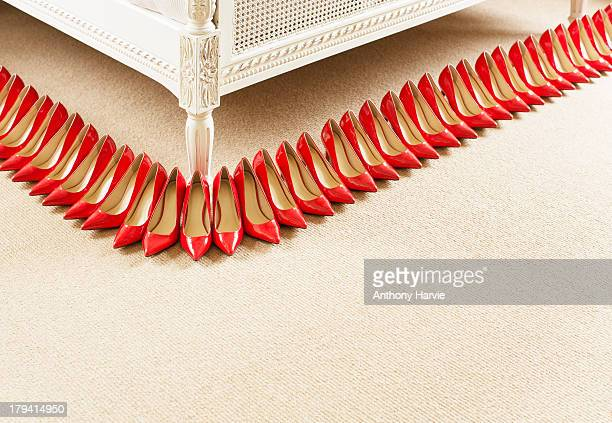 Red shoes in a row next to bed