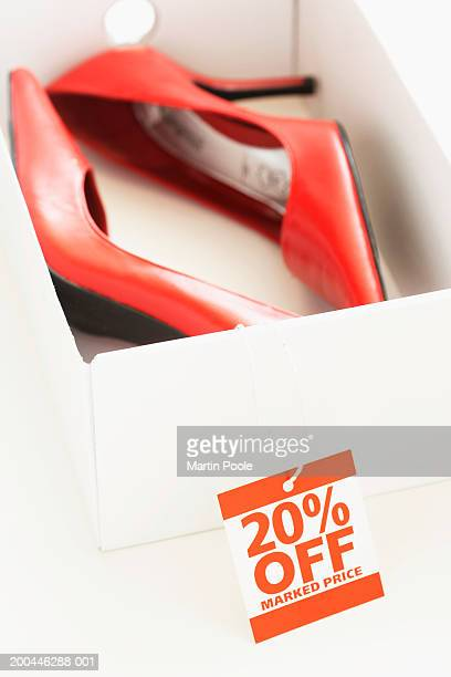 Red shoes in box with sale tag attached, close-up