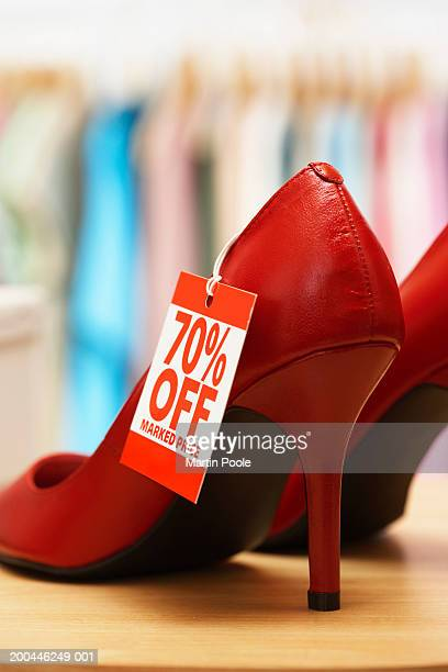 Red shoes on shop counter with discount tag attached, close-up