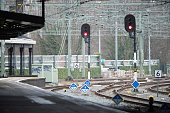 Red signal lights on railway seen from train platform.