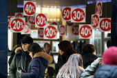 Red signs show varying discounts as they hang above retail displays inside a shoe store on the first day of the New Year sales in Rome Italy on...
