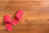 A pair of red slippers on the wooden floor