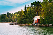 Red Small Finnish Wooden Sauna Log Cabin On Island In Autumn Season.