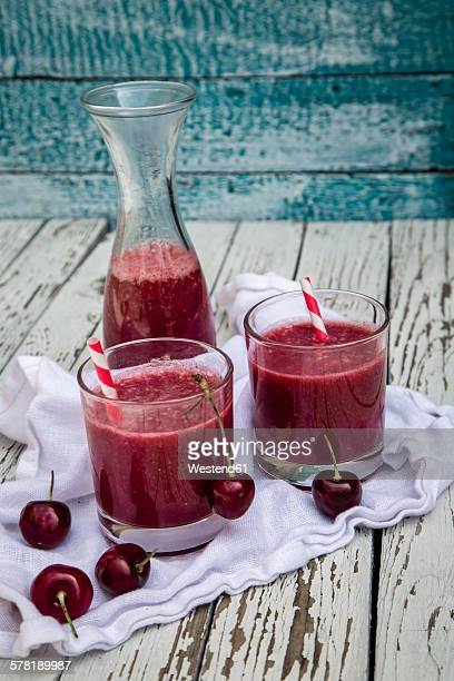 Red smoothie in glasses, cherries on wood