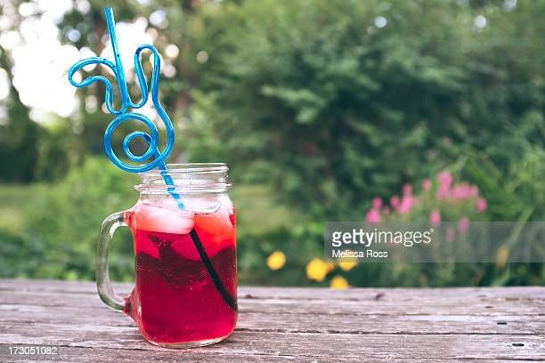 Red soda or punch in a glass jar mug with a straw