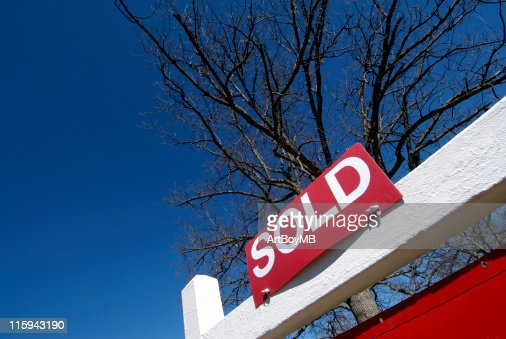 Red sold sign with tree in the background