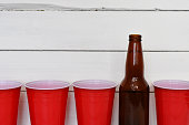 A close up image of red solo drinking cups and brown beer bottles.