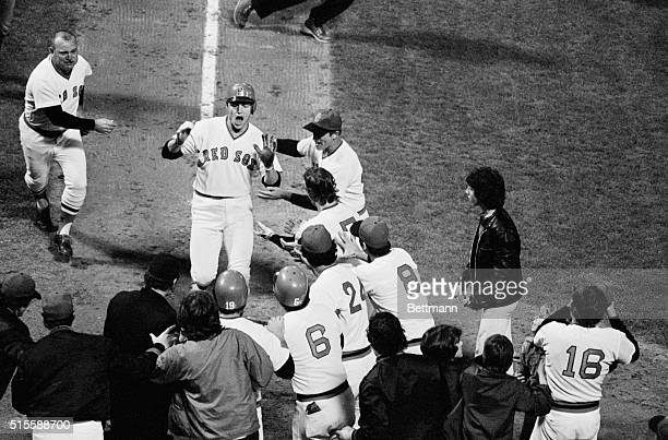 Red Sox catcher Carlton Fisk is greeted by his teammates at home plate after hitting the scoring run in game 6 of the 1975 World Series against the...