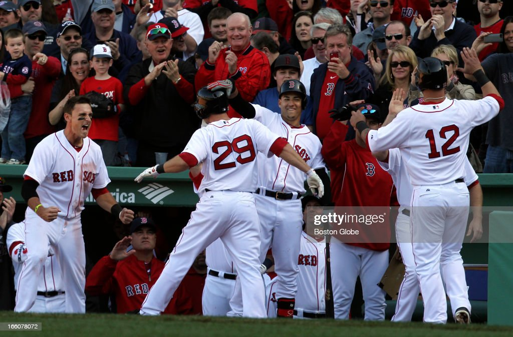 Red Sox Daniel Nava greeted by happy teammates and fans after his three run-homer in the seventh inning. The Baltimore Orioles play the Boston Red Sox during Opening Day at Fenway Park.