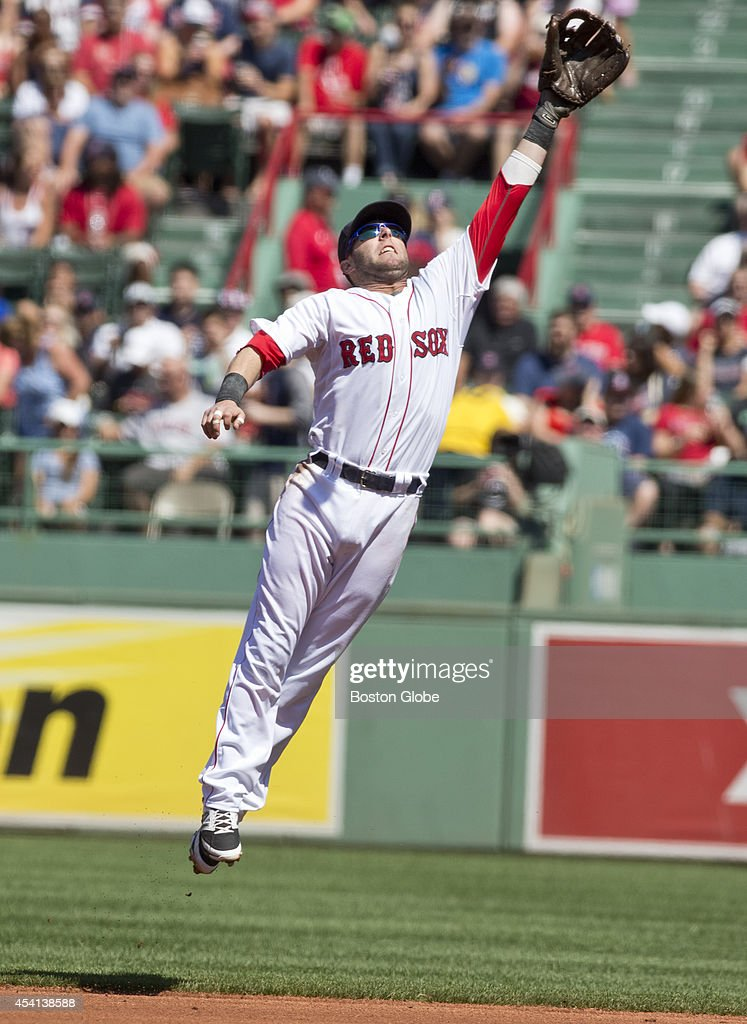 Red Sox Dustin Pedroia cannot catch Seattle Mariners Logan Morrison's run batted in base hit during first inning action at Fenway Park on Sunday, August 24, 2014.
