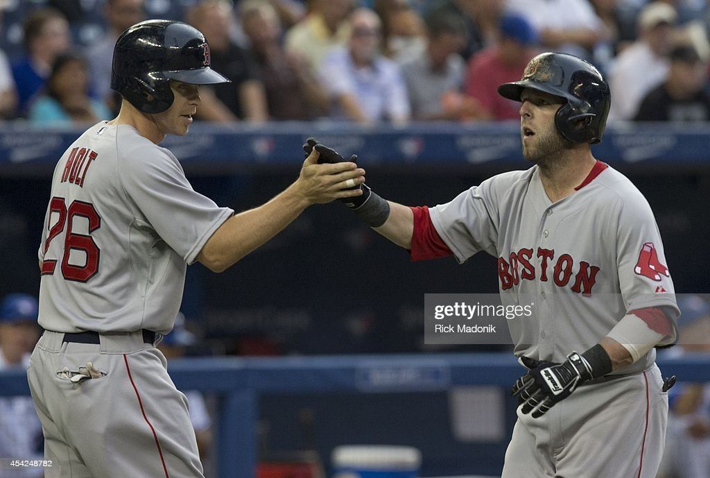 TORONTO - AUGUST 26 - Red Sox Dustin Pedroia (right) is greeted at home by Brock Holt after Pedroia's 2 run homer in the 1st inning. Toronto Blue Jays Vs Boston Red Sox during MLB action at Rogers Centre on August 26, 2014.