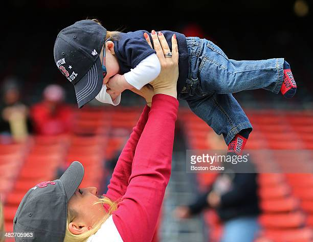 Red Sox fan Andrea Colby from Hyde Park holds her son Matthew 5 months wearing Red Sox socks over her head before the game The Boston Red Sox hosted...